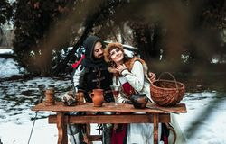 Man and woman in historical costumes at a wooden table royalty free stock photography