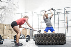 Man and woman hitting tire with sledgehammer in crossfit gym Royalty Free Stock Image