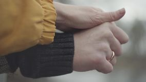 Man and woman hold hands outdoors on the blurred background. Gold ring is on the man finger. Lovely couple in warm coats. Man and woman hold hands outdoors on stock footage