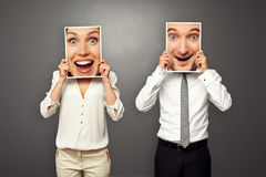 Man and woman holding amazed happy faces. Man and women holding amazed happy faces. concept photo over grey background Royalty Free Stock Image