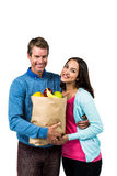 Man and woman holding bag of fruits Stock Photos