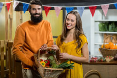 Man and woman holding a basket of vegetables at the grocery store. Portrait of a man and woman holding a basket of vegetables at the grocery store royalty free stock images