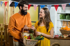 Man and woman holding a basket of vegetables at the grocery store. Smiling man and woman holding a basket of vegetables at the grocery store stock photography