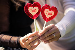 Man and woman holding candy. In the shape of a heart in the park royalty free stock photos