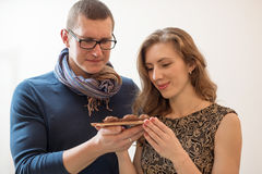 Man and woman holding chocolate truffle Royalty Free Stock Photography
