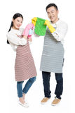Man and woman holding cleaning supplies Royalty Free Stock Images
