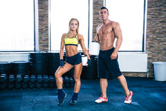 Man and woman holding container with protein at gym. Muscular men and sporty women holding container with protein at gym Royalty Free Stock Image