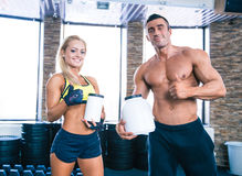 Man and woman holding container with sports nutrition. Muscular men and sporty women holding container with sports nutrition and showing thumb up Stock Photo