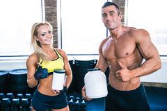 Man and woman holding container with sports nutrition. Man and women holding container with sports nutrition and showing thumb up at gym Royalty Free Stock Image