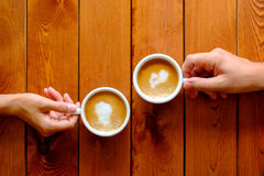 Man and woman holding a cup of coffee in a cafe, top view Royalty Free Stock Images