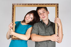 Man and woman holding frame and standing inside it Royalty Free Stock Photos