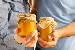 Man and woman holding glass jars of honey Royalty Free Stock Images