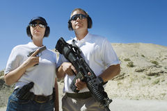 Man And Woman Holding Guns At Firing Range. Confident men and women holding guns at firing range in desert Stock Images