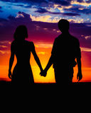 Man and woman holding hands on the background of a beautiful sun. Set Royalty Free Stock Photography