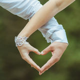 Man and woman holding by hands and making love hea Royalty Free Stock Photography