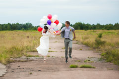 Man and woman holding in hands many colorful latex balloons. Head and shoulders portrait of happy cheerful couple. Man and women holding in hands many colorful stock image