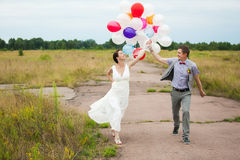 Man and woman holding in hands many colorful latex balloons. Head and shoulders portrait of happy cheerful couple. Man and women holding in hands many colorful royalty free stock images