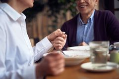 Man and woman holding hands sitting in cafe. Enjoyable meetings. Close up cropped head portrait of aged elegant happy gentleman holding hand of lady while having stock photography