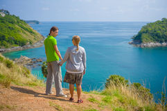 Man and woman holding hands on tropical island cliff Royalty Free Stock Image