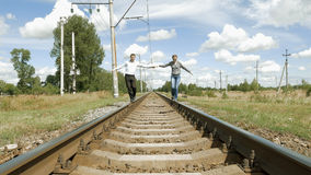 Man and woman holding hands walking along railway Royalty Free Stock Image