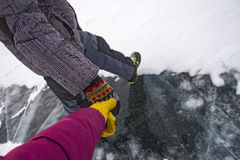 Man and woman holding hands in the winter on the ice of Lake Baikal. Royalty Free Stock Image