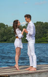 Man and woman holding hands on a wooden pier near the water. Stock Photos