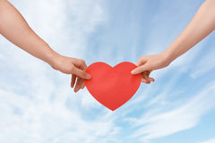 Man and woman holding a heart. Against the blue sky. the concept of love and relationships Stock Photography