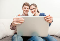 Man in woman holding laptop and looking over it at camera Royalty Free Stock Photos