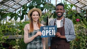 Man and woman holding we are open sign in greenhouse smiling looking at camera. Man and woman happy business partners are holding we are open sign in greenhouse stock video footage