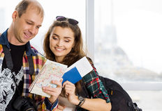 Man and a woman holding a passport .Look at the map, direction of study. Europeans. Gathered in a guided tour.Honeymoon. A young men and a women holding a Stock Image