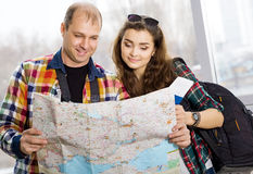 Man and a woman holding a passport .Look at the map, direction of study. Europeans. Gathered in a guided tour.Honeymoon Royalty Free Stock Images