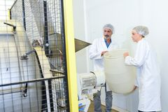 Man and woman holding plastic tub next to industrial machine stock image