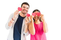 Man And Woman Holding Red Paper Hearts Against Plain Background. Happy young boyfriend and girlfriend having fun with hearts against white background stock photography