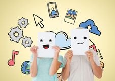 Man and woman holding smiley faces over their face with various icons in background. Digital composition of men and women holding smiley faces over their face Royalty Free Stock Photos