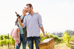 Man with woman holding wine bottle and basket Stock Image