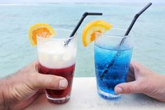 Man and woman holds a red and blue cocktail drinks with ice serv. Hands of a man and woman holds a red and blue cocktail drinks with ice served over a lagoon of Stock Images