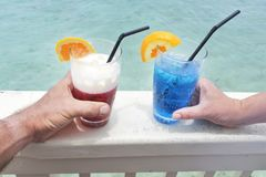 Man and woman holds a red and blue cocktail drinks with ice serv. Hands of a man and woman holds a red and blue cocktail drinks with ice served over a lagoon of Stock Image
