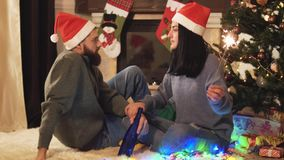 Man and woman sitting near christmas tree, woman holding sparklers in hand. Man holding alcohol bottle. Sparkler burns. Man and woman in home clothes sitting stock footage