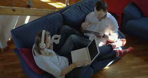 Man and woman at home using pad and laptop. High angle shot of young couple lying on the sofa at home. Woman in headphones using laptop and having tea while stock video