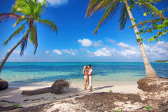 Man and woman - honeymoon on tropical island. Man and women - romantic meeting on the ocean shore with palms royalty free stock photo
