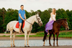 Man and woman with a horses at the sea. Romantic love. Royalty Free Stock Photo