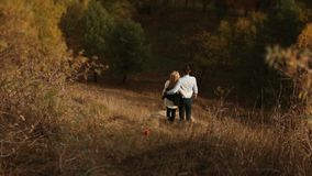Man and woman hug each other watching old city over the autumn trees stock footage