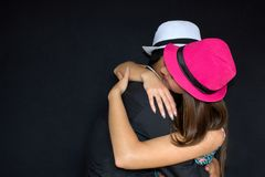 Man and woman hugging in hats on a black background. Strong embrace. royalty free stock photo
