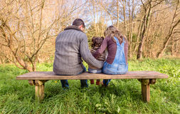 Man and woman hugging little girl sitting on a Royalty Free Stock Photos
