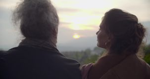 Man and woman hugging relaxing and talking into car looking sunset.Back close shot.Rear view. Caucasian couple in love. Roadtrip vacation italian travel on stock video