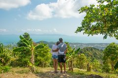 Man and woman hugging at tropical viewpoint looking at breathtaking view, back view royalty free stock images