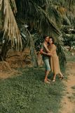 Man and woman hugging under palm trees Stock Photo