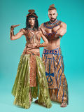 The man, woman in the images of Egyptian Pharaoh and Cleopatra. The men and women in the images of Egyptian Pharaoh and Cleopatra on blue studio background Royalty Free Stock Photos