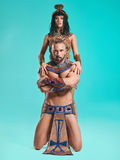 The man, woman in the images of Egyptian Pharaoh and Cleopatra. The men and women in the images of Egyptian Pharaoh and Cleopatra on blue studio background stock photography