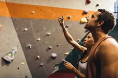 Man and woman at an indoor rock climbing gym. Female instructor giving instructions to a men on wall climbing. Man learning the art of rock climbing at an indoor stock photo